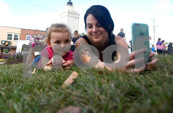 10/6/2017 Mike Orazzi | Staff Samantha Newberry and her daughter Autumn sit in the grass during the 49th Apple Harvest Festival in Southington Friday evening.