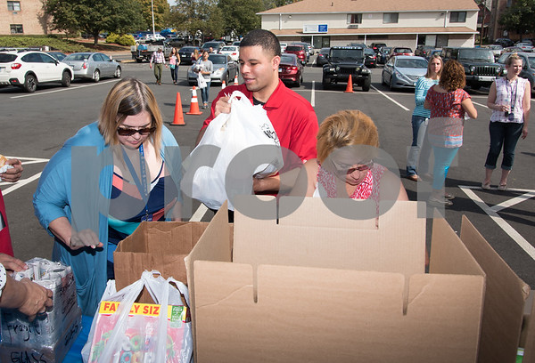 10/06/17 Wesley Bunnell   Staff CMHA and Puerto Rican Society of New Britain held a relief drive at CMHA on Whiting St on noon on Friday. Alderman Kristian Rosado carries a bag donated from the parking lot to the donations bin.