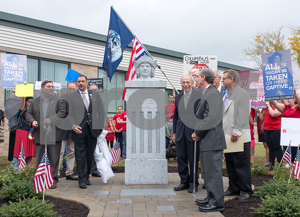 A ceremony was held on Monday morning at the Southington Municipal Center for the dedication and unveiling of the Christopher Columbus Monument honoring the 525th anniversary of the discovery of America. Protestors hold up signs behind the statue during the ceremony.