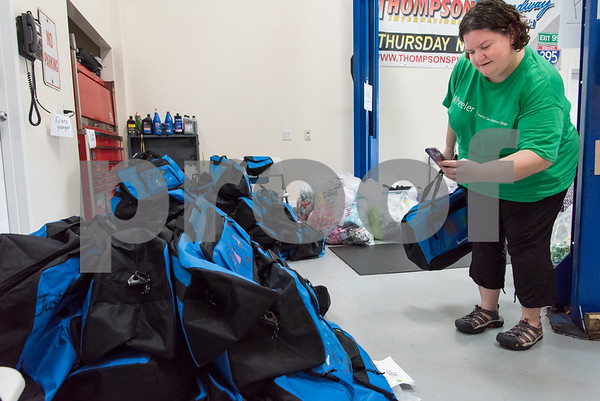 10/09/17 Wesley Bunnell | Staff Volunteers from the Mott Corporation donated their time and items to stuff duffle bags for kids in Wheeler Clinic's foster care program. Wheeler Clinic employee Anne Russo takes a photo of completed bags.