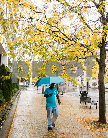10/09/17 Wesley Bunnell | Staff Anthony McBride of New Britain walks under a canopy of brightly colored leaves while waiting for the bus in downtown New Britain on Monday afternoon.