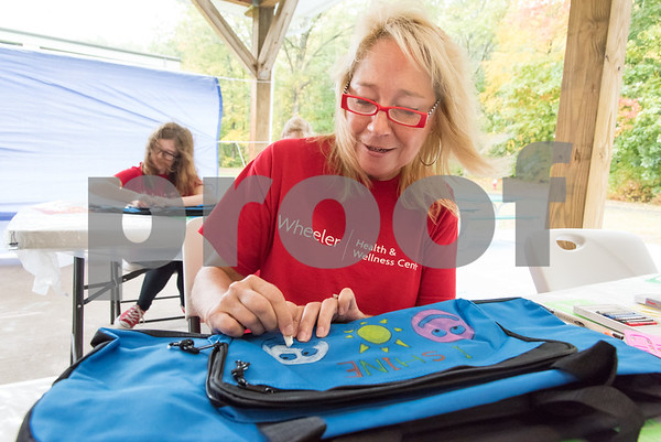 10/09/17 Wesley Bunnell | Staff Volunteers from the Mott Corporation donated their time and items to stuff duffle bags for kids in Wheeler Clinic's foster care program. Motts employee Patty Cruickshanks decorates a bag.