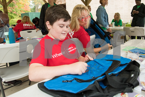 10/09/17 Wesley Bunnell | Staff Volunteers from the Mott Corporation donated their time and items to stuff duffle bags for kids in Wheeler Clinic's foster care program. Motts employee Patty Cruickshanks leans over to say good job to Jacob Darrell, age 11, as he decorates a duffle bag.