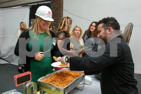 10/19/17 Wesley Bunnell | Staff CMHA held their annual meeting at their new location on Main St. across from Central Park in downtown New Britain. Karolina Wytrykowska wears a hard hat which was the theme of the evening as she is served by Mofongo owner Vincent Placeres.