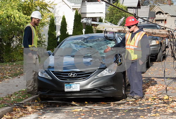 10/30/17 Wesley Bunnell | Staff At approximately 8:30pm on Sunday night a falling tree took down a utility pole and its electric lines causing a transformer to explode startling residents on Summer St. A utility pole fell severely damaged a black Hyundai. Workers from Clean Harbors and Eversource assess the damage.