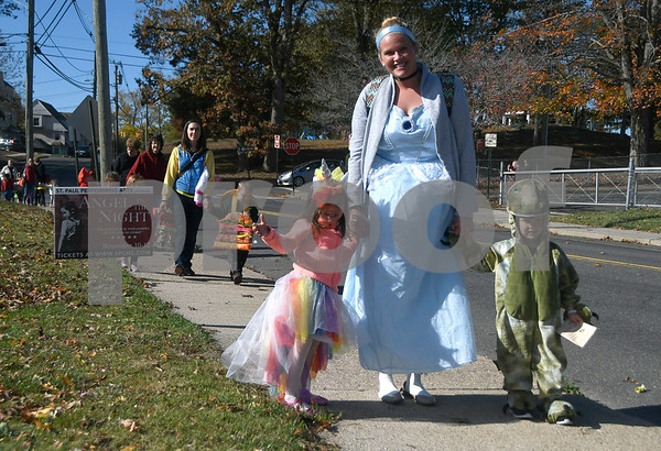 10/31/2017 Mike Orazzi | Staff St. Joseph School's Ashley Hill leads costumed students Veronica Poulin and Noah Frenette on their way from the Bristol Public Library back to the school Tuesday morning.