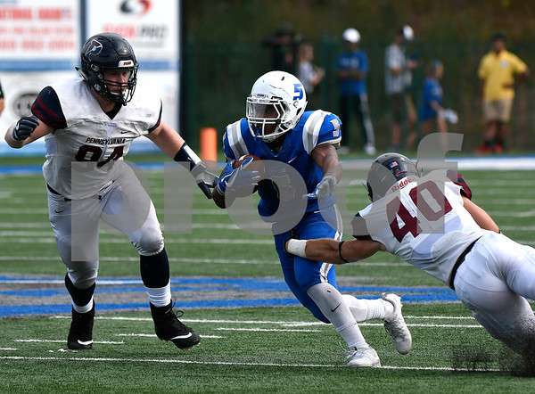 10/7/2017 Mike Orazzi | Staff CCSU's Cameron Nash (5) and the Penn Quakers' Tayler Hendrickson (94) and Luke Bullock (40) Saturday in New Britain.
