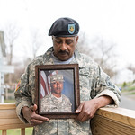032316   Wesley Bunnell   Staff  Wearing his son Julian's Army jacket and beret Selwyn Cartie stands on his front porch holding Julian's photo & discussing the circumstances of his death.