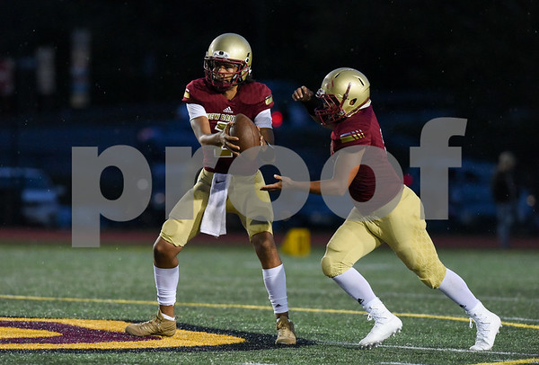 09/08/17 Wesley Bunnell | Staff New Britain High School football vs Conard at Veteran's Stadium on Friday evening. Quarterback Jahfari Newman (2) hands off to running back Shawn Robinson (3).
