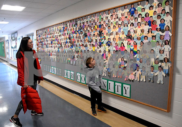 9/30/2017 Mike Orazzi | Staff Jennifer D'Esopo and her son Matthew look at pictures of students and staff in the hallway during the open house at the Ivy Drive School's 50th anniversary celebration Saturday in Bristol.