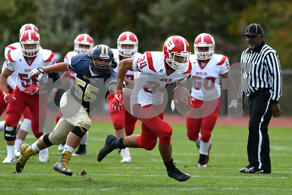 9/30/2017 Mike Orazzi | Staff Berlin's Alexander Halkias (34) and RHAM's Drew Smith (55) during Saturday's football game in Hebron.